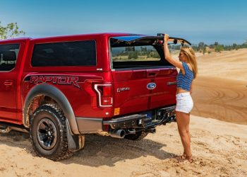 women on a beach opening the back window of her CX Revo truck cap on her red pick-up truck