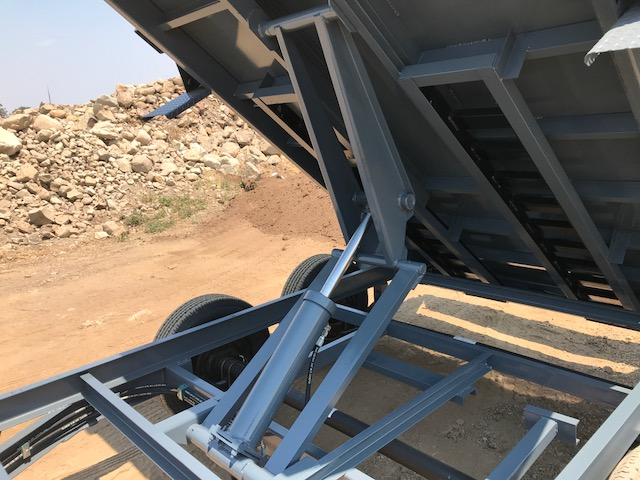 The Iron Panther dump trailer raised with a close look at the industry-grade scissor lift