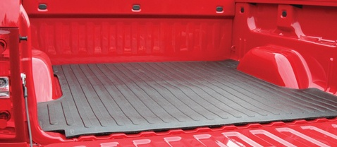 Red pickup truck bed with black rubber bed mat.