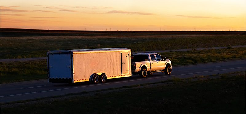 pick-up truck towing a large trailer with a rear mounted trailer hitch on an open highway at sunset