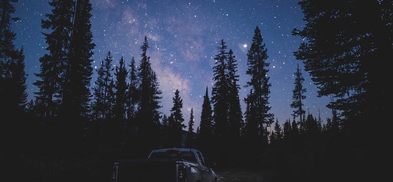 Adventure Truck with Milky Way above behind pine trees