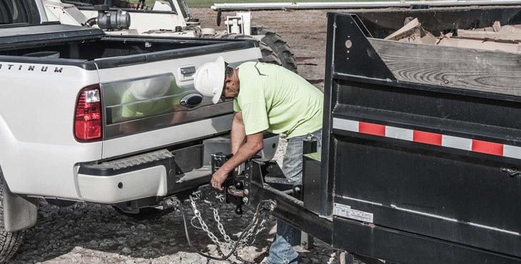 construction worker hitching a railer of work materials to his white pick-up trick with a ball mount hitch