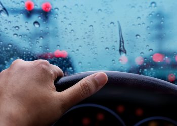 hand on steering wheel during rainy day