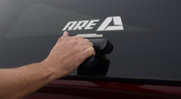 male hand opening the back window of cx revo truck cap with one motion handle