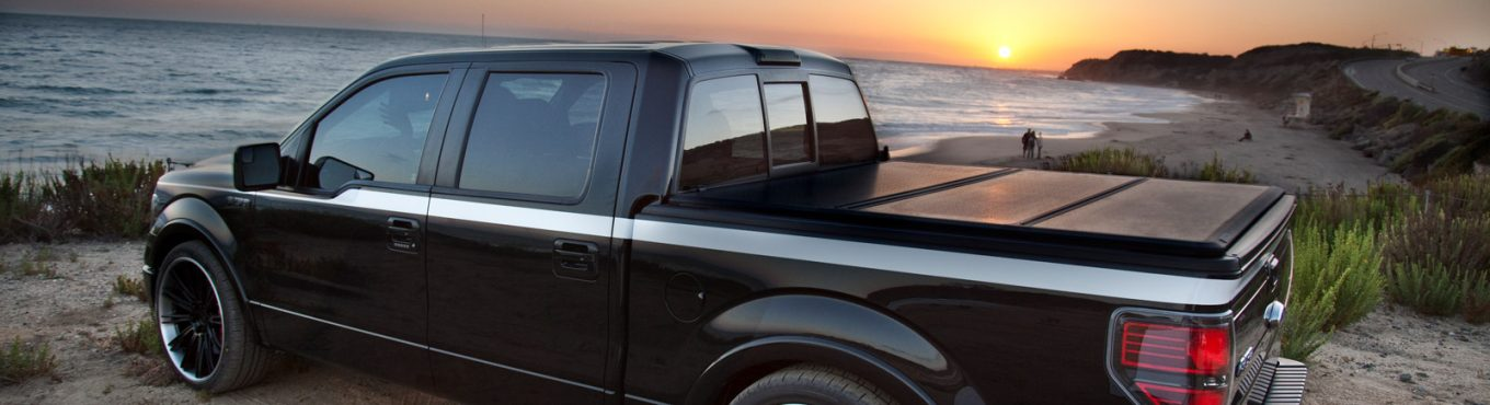 pickup truck parked on beach equipped with folding tonneau cover