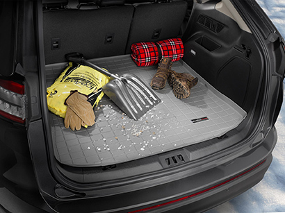 open trunk of an SUV with a weather proof cargo loner, snow shoes, gloves, shovel, and salt to melt snow.